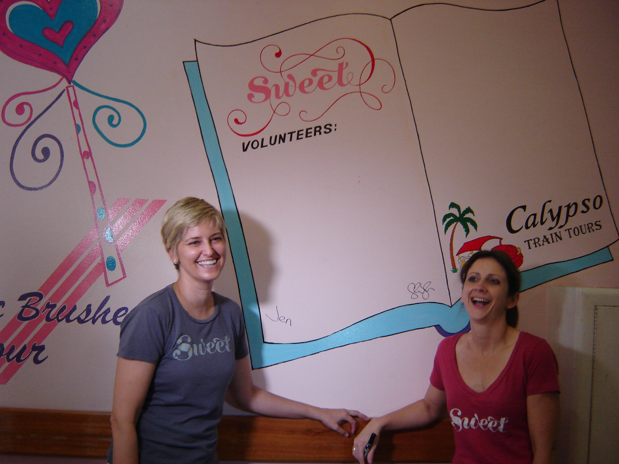 "Sweet co-founders Jennifer Rainin, left, and Shannon Wentworth stand by a wall demonstrating the cheer ""Sweeties"" brought to the pediatric ward at the Karl Heusner Memorial Hospital in Belize City, Belize. Volunteers from the ship helped paint the ward. (Photo: Super G)"