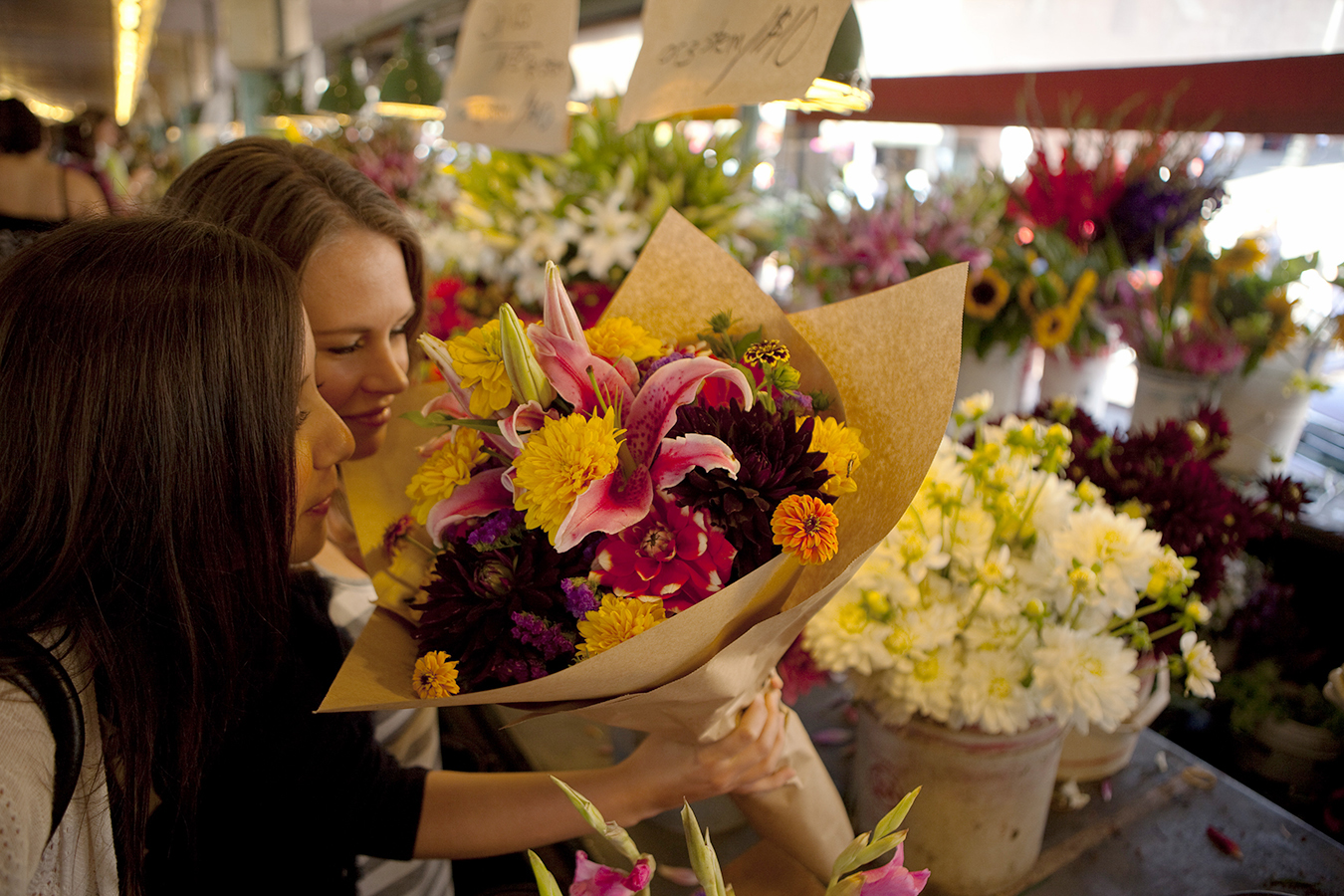 Two women selecting flowers for their wedding at Pike Place Market in Seattle. (Photo: Courtesy of Visit Seattle)