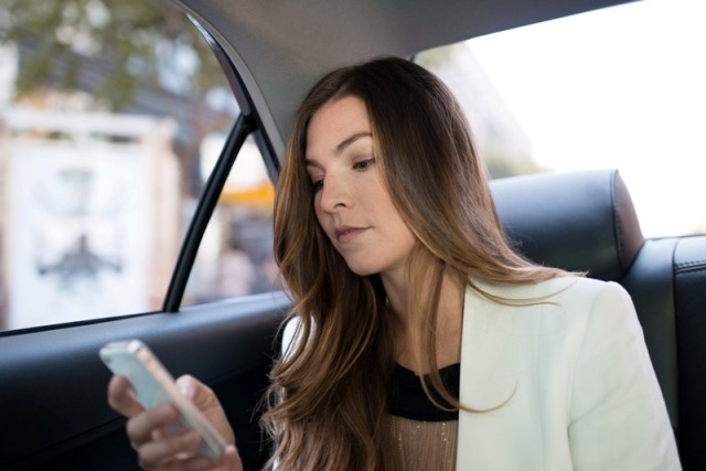 Woman riding in the back seat of an Uber car