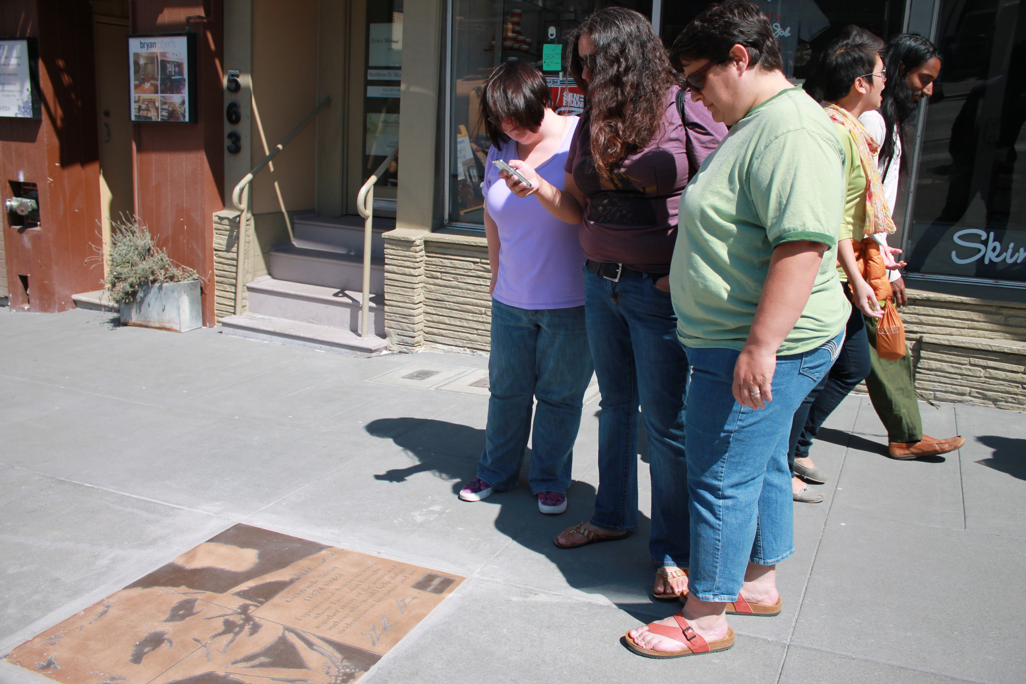 Former San Francisco Assistant District Attorney Rebecca Prozan, foreground, her wife, attorney Julia Adams, background, and their friend, center, pause to read the plaque honoring American lesbian writer Gertrude Stein outside of Hand Job Nails and Spa on Castro Street near 19th Street. (Photo: Heather Cassell)