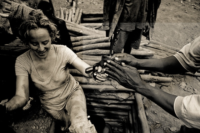 Humanitarian photographer Lisa Kristine being helped out of a mine shaft in Ghana. (Photo: Courtesy of Lisa Kristine Gallery)
