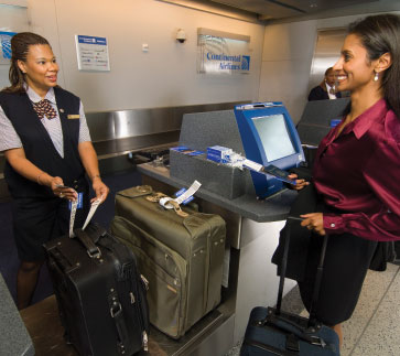 A woman checks in her luggage at the ticket counter. (Photo: Courtesy of FutureTravelExperience.com)