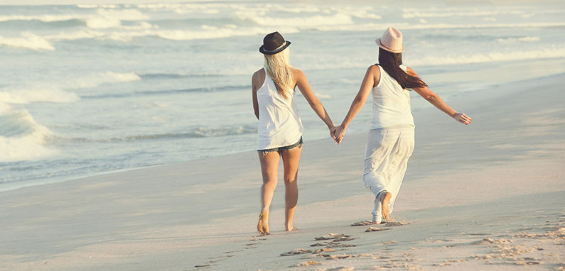 Taking a romantic walk along the beach during a Caribbean vacation. (Photo: Courtesy of IGLTA)