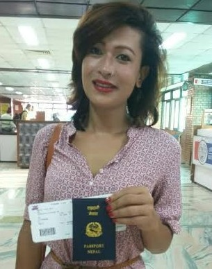 "Bhumika Shrestha proudly holds up her passport as the first transgender person to fly using her new passport that denotes ""other"" as her gender, as she boards a plane to New Delhi, India on Tuesday, October 6. (Photo: Courtesy of the Blue Diamond Society)"