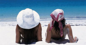 Girls basking in the sun on soft sandy beaches.