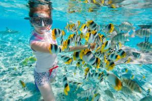 A girl swims with fishes in Thailand. (Photo: Courtesy of Experience Travel Group)
