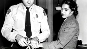 Rosa Parks being arrested for refusing to give up her seat on a bus in 1955.