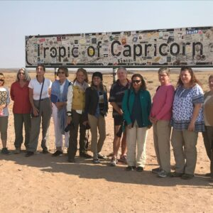 """Guests of the Women's Travel Group take a group photo beneath the """"Tropic of Capricorn"""" sign in Namibia, Africa."""