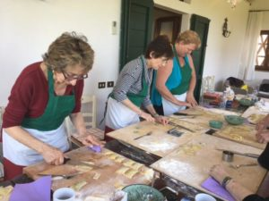 Guests of the Women's Travel Group making ravioli's in Tuscany, Italy.